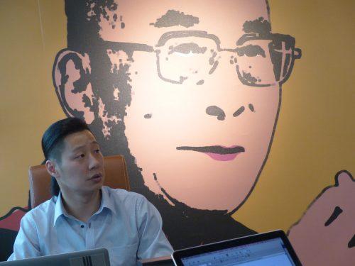 Freddy Lim in seinem Büro vor einem Bild des Dalai Lama